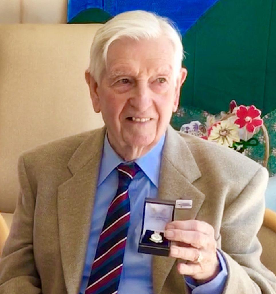 Andrew Gauld holding his Veterans Badge.